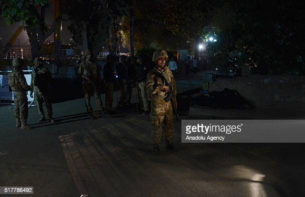 Pakistani security forces take secuirty measures at the explosion site after a suicide bomber blew himself up in a crowded park in Lahore killing at...