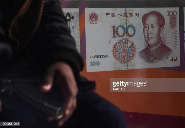 A Pakistani security guard sits outside the currency exchange shop in Lahore on January 3 2018 Pakistan will allow the Chinese yuan to be used for...