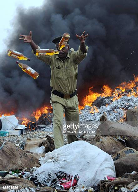 A Pakistani security member throws bottles of alcoholic drinks to be destroyed in a fire for liquor and contraband narcotics on the outskirts of...