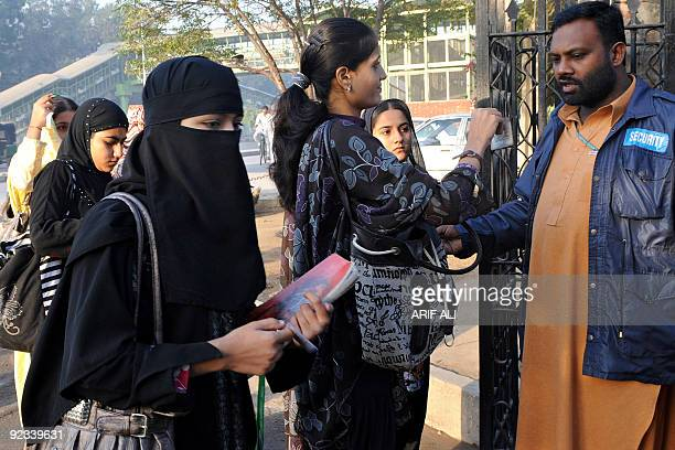 Pakistani security official checks identity cards of students as they enter their college campus in Lahore on October 26 following the college's...