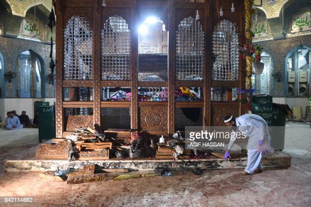 A Pakistani security official collects evidence a day after a bomb attack hit the 13th century Muslim Sufi shrine of Lal Shahbaz Qalandar in the town...