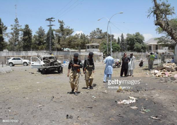 Pakistani Security officials and people inspect at the site of suicide bomb blast in Quetta Pakistan on June 23 2017 At least 12 people were killed...