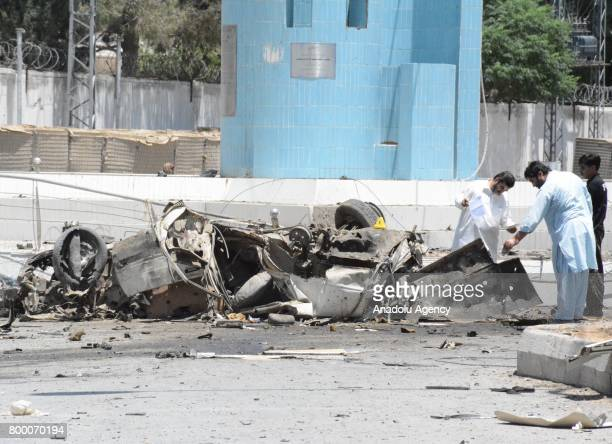 Pakistani Security officials and people inspect at the site of suicide bomb blast in Quetta, Pakistan on June 23, 2017. At least 12 people were...