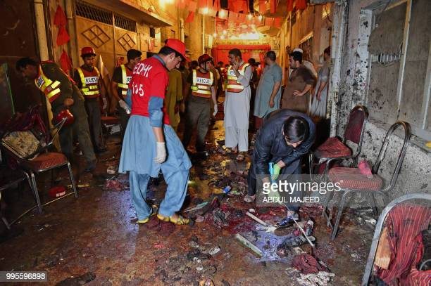 Pakistani security officials and volunteers search the site after a suicide bombing at an election rally in Peshawar on July 10 2018 A suicide...