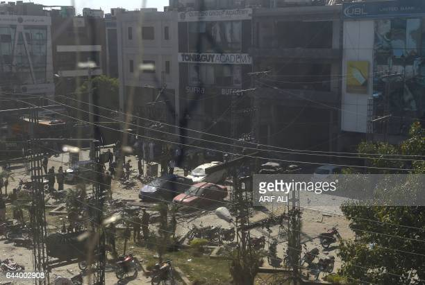 Pakistani security officials cordon off the site of a bomb attack in an upscale shopping area that includes an academy for the international hair...