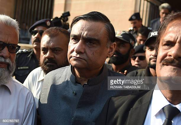 Pakistani security officials escort expetroleum minister Asim Hussain a close aide to former president Asif Zardari as they leave the court after...