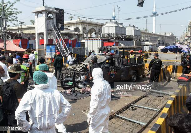 Pakistani security officials examine the site of a bomb blast outside a Sufi shrine in Lahore on May 8 2019 A blast at one of Pakistan's oldest and...
