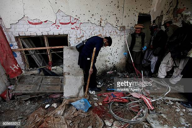 Pakistani security officials examine the site of a suicide bomb attack in Peshawar on January 19 2016 At least 11 people were killed and 21 injured...
