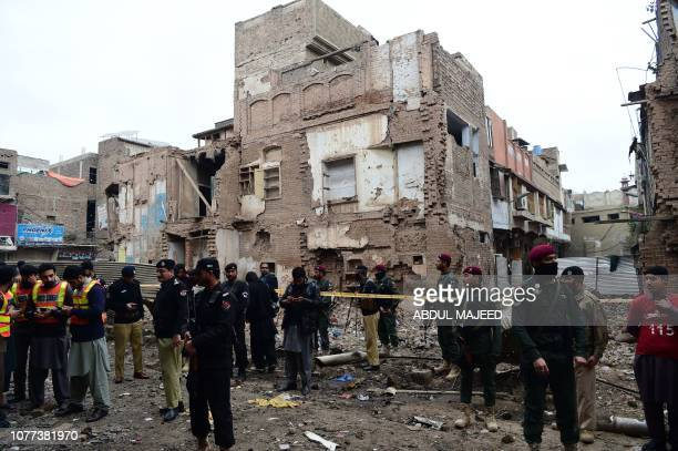 Pakistani security officials examine the site of an explosion at a market area in Peshawar on January 5 2019 A car bomb injured six people in...