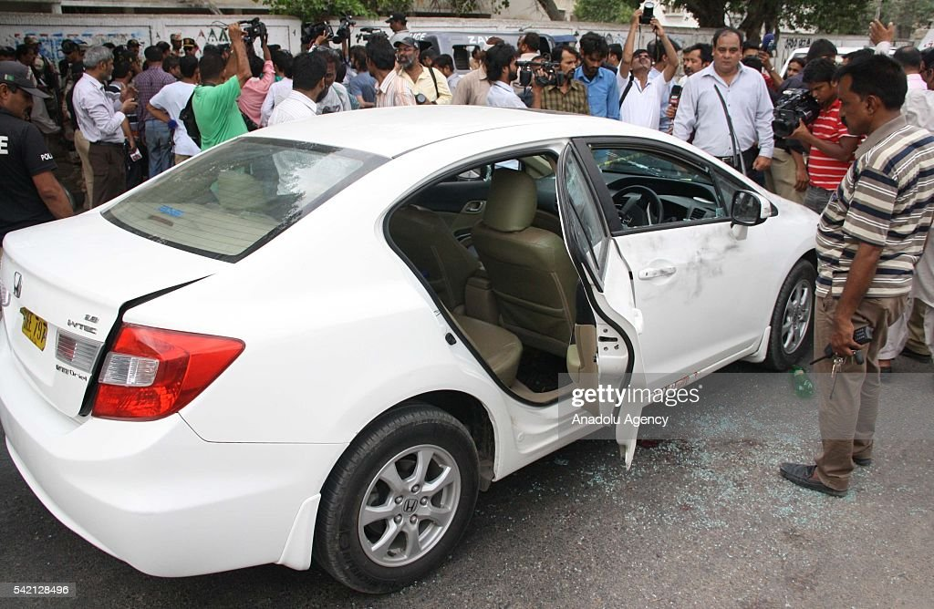 Pakistani security officials gather around the bullet-riddled car of Sufi musician Amjad Sabri who was killed in an attack by unknown gunmen in Karachi on June 22, 2016