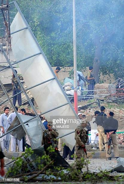 Pakistani security officials gather beside the destroyed building of the police Criminal Investigation Department following a suicide bomb attack in...
