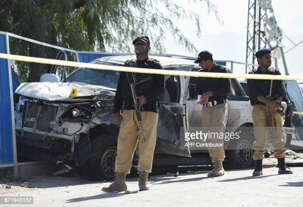 Pakistani security officials inspect a destroyed vehicle of a police officer at the site of a suspected suicide bomb attack in Quetta on November 9...