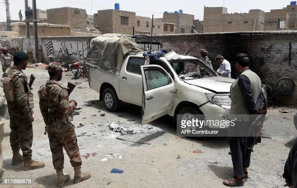 Pakistani security officials inspect a vehicle at the site of a bomb explosion targeting the police chief in the border town of Chaman on July 10...