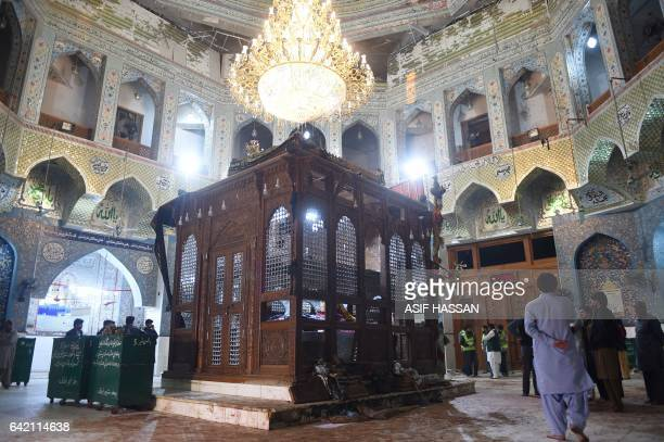 Pakistani security officials inspect the bloodstained floor a day after a bomb attack hit the 13th century Muslim Sufi shrine of Lal Shahbaz Qalandar...