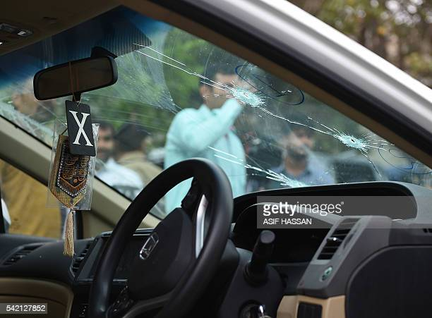 Pakistani security officials inspect the bulletriddled car of Sufi musician Amjad Sabri who was killed in an attack by unknown gunmen in Karachi on...