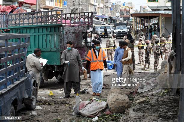 TOPSHOT Pakistani security officials inspect the site of a bomb blast at a fruit market in Quetta on April 12 2019 At least 16 people were killed and...