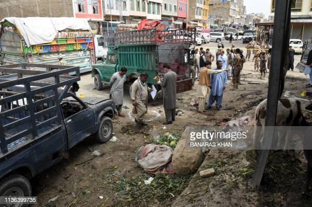 Pakistani security officials inspect the site of a bomb blast at a fruit market in Quetta on April 12 2019 At least 16 people were killed and 30...