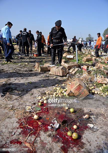 Pakistani security officials inspect the site of a bomb explosion in a fruit and vegetable market in Islamabad on April 9 2014 A bomb explosion...
