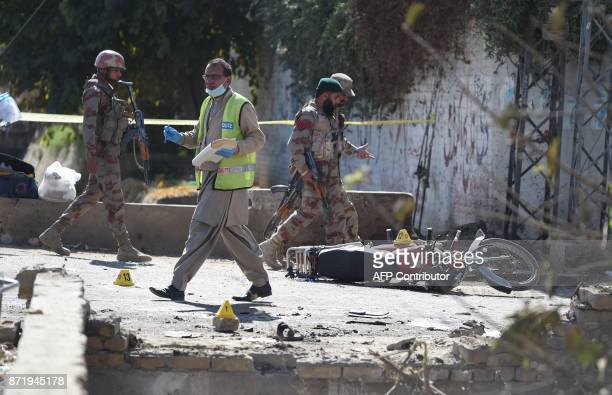 Pakistani security officials inspect the site of a suspected suicide bomb attack on a police officer's vehicle in Quetta on November 9 2017 A...