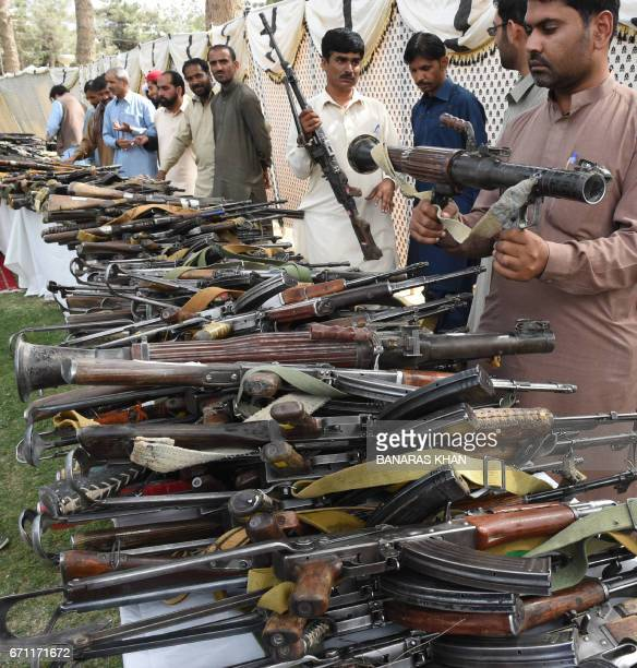 Pakistani security officials inspect weapons after Baloch militants hended over their weapons and they surrendered to Pakistani security forces in...