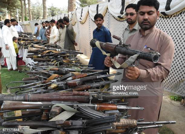Pakistani security officials inspect weapons after they were handed over by Baloch militants when they surrendered to Pakistani security forces in...