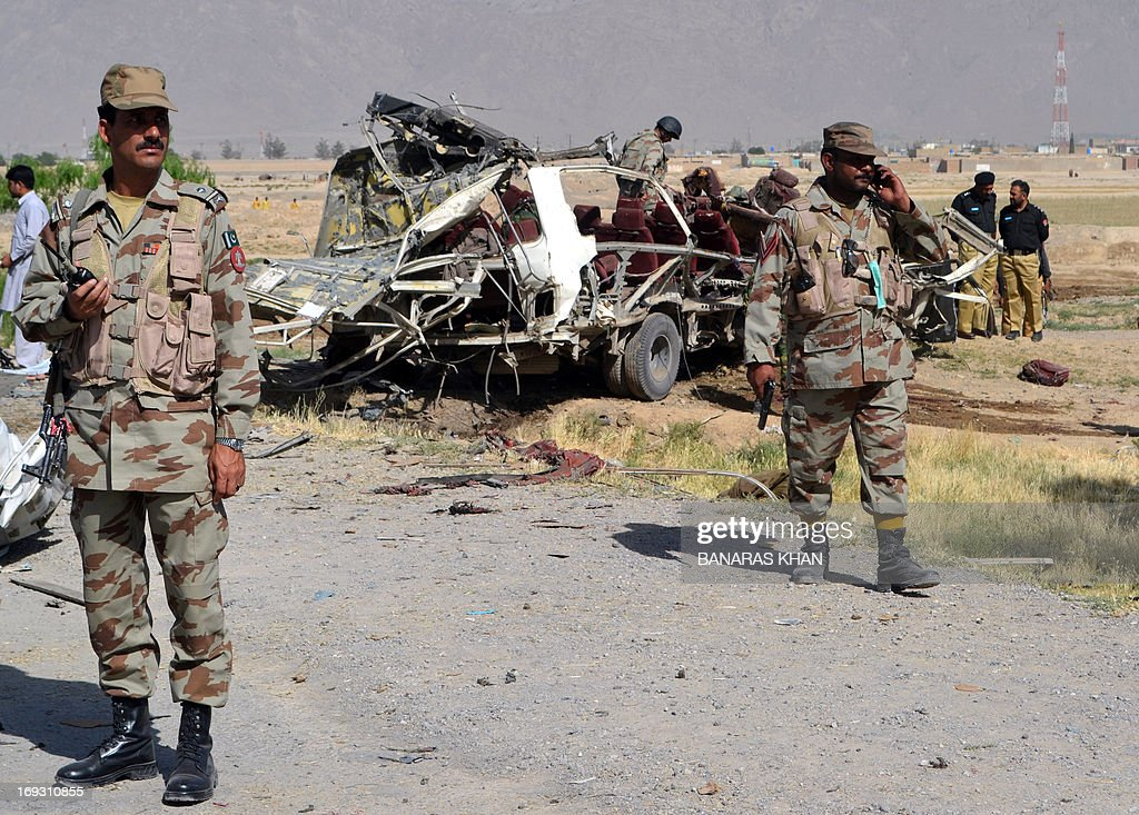 Pakistani security officials keep watch near a destroyed vehicle used by security forces following a bomb attack on the outskirts of Quetta, the capital of restive Baluchistan province, on May 23, 2013. A bomb planted in a rickshaw tore through a vehicle used by security forces in southwest Pakistan on May 23, killing at least 12 people, police said.