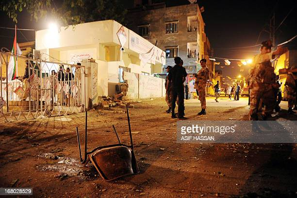 Pakistani security officials stand guard at the site of twin bomb blasts near the secular Muttahida Qaumi Movement party office in Karachi on May 4...