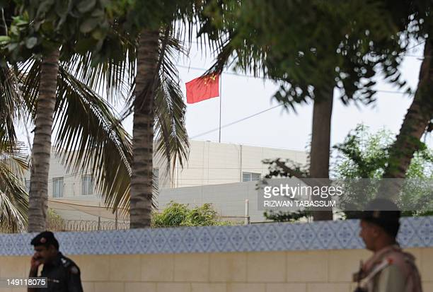 Pakistani security officials stand guard outside the Chinese consulate following a bomb blast near the premises in Karachi on July 23 2012 No...