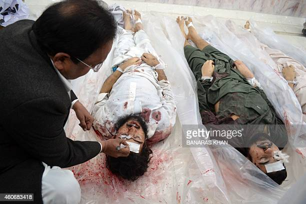 A Pakistani security personal gives number to a militant body killed in operation at a hospital in Quetta on December 19 2014 At least seven...