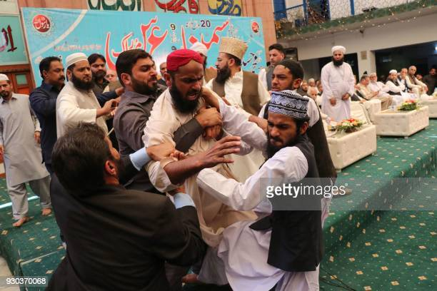 Pakistani security personnel and organiser hold a student after he hurled a shoe at former Prime Minister Nawaz Sharif during a ceremony in Lahore on...