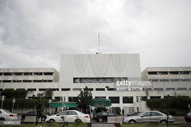 Pakistani security personnel and other officials gather outside the Parliament House building during the last session of the parliament in Islamabad...