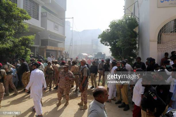 Pakistani security personnel are seen at the site of a passenger plane crash in Karachi, Pakistan, May 22, 2020. A Pakistani passenger plane with at...
