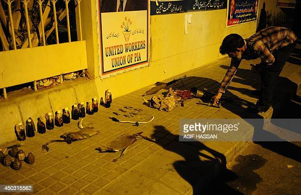A Pakistani security personnel arrange seized weapons after militants attacked Jinnah International Airport in Karachi on June 9 2014 Pakistan's...