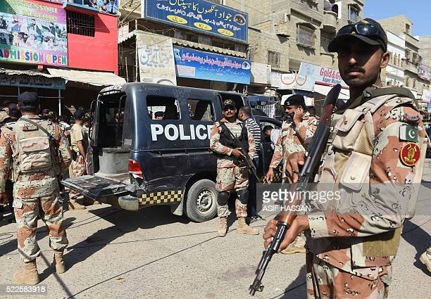 Pakistani security personnel gather around a police van after an attack by gunmen on security members guarding a polio vaccination team in Karachi on...