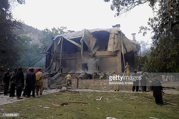 Pakistani security personnel gather as firefighters extinguish a blaze which gutted a historical building in Ziarat 80 kilometres southeast of Quetta...