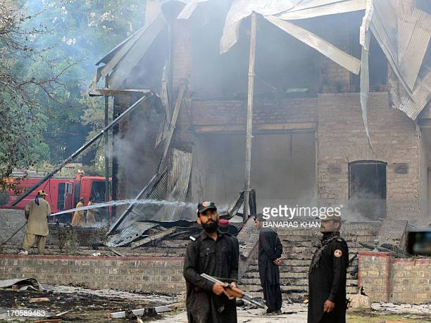 Pakistani security personnel look on as firefighters extinguish a blaze which gutted a historical building in Ziarat 80 kilometres southeast of...