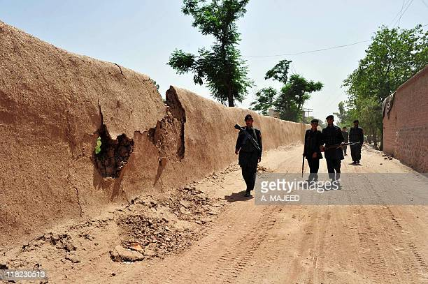 Pakistani security personnel patrol near a damaged police checkpoint following an attack by militants on the outskirts of Peshawar on May 18 2011...