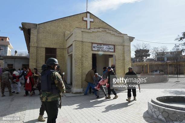 TOPSHOT Pakistani security personnel rescue an injured woman after suicide bombers attacked a Methodist church during a Sunday service in Quetta on...