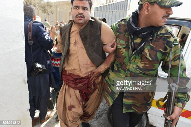 Pakistani security personnel rescues a an injured man after suicide bombers attacked a Methodist church during a Sunday service in Quetta on December...