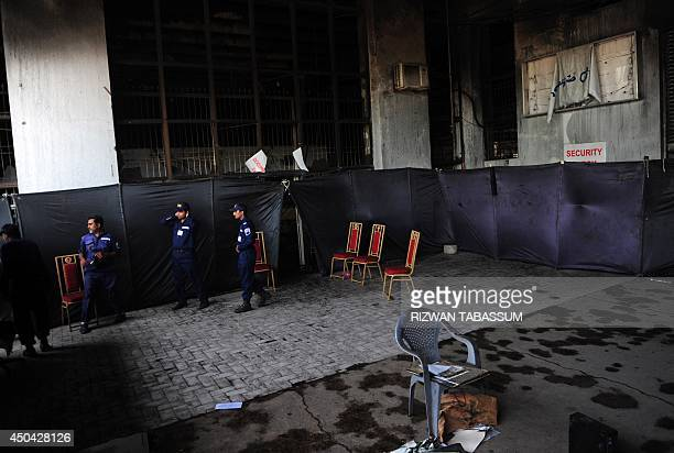 Pakistani security personnel stand at a burnt storage facility at the Jinnah International Airport in Karachi on June 11 2014 Uzbek fighters were...