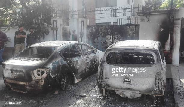 TOPSHOT Pakistani security personnel stand next to burned out vehicles in front of the Chinese consulate after an attack in Karachi on November 23...