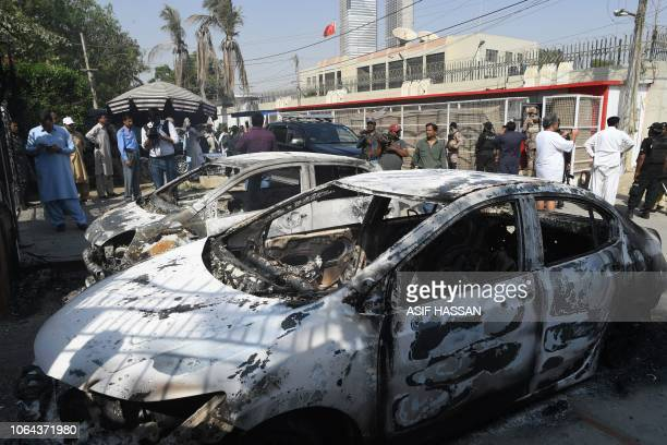 Pakistani security personnel stand next to burned out vehicles in front of the Chinese consulate after an attack in Karachi on November 23 2018 At...