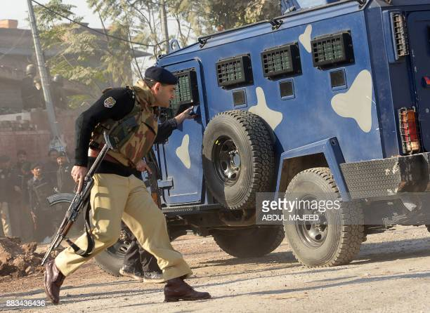 Pakistani security personnel take position outside an Agriculture Training Institute after an attack by Taliban militants in Peshawar on December 1...