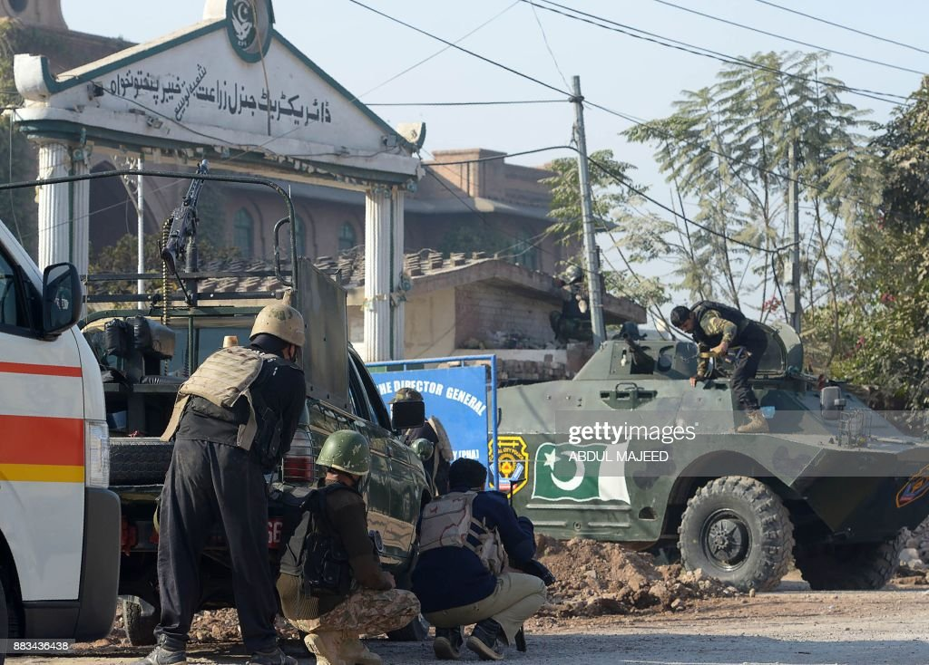 Pakistani security personnel take position outside an Agriculture Training Institute after an attack by Taliban militants in Peshawar on December 1, 2017. Taliban militants stormed a training institute in Pakistan's northwestern city of Peshawar Friday, injuring at least seven people, as the country marked the birthday of the Prophet Mohammed. MAJEED