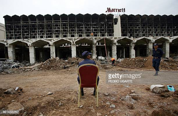 A Pakistani security sits on a chair placed among the wreckage of the devastated Marriott Hotel in Islamabad on September 22 2008 two days after a...