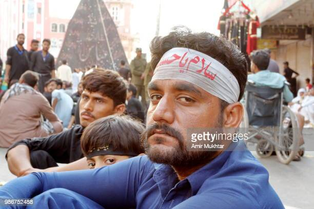 Pakistani Shia Muslim tied a headband name written of Hazrat Imam Hussain on it and resting before the self-flagellation of the main bazar of clock tower during a Muharram procession on road