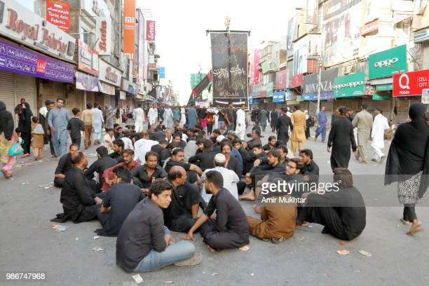 Pakistani Shia Muslims carrying flags and resting before the self-flagellation on the main bazar of clock tower during a Muharram procession on road