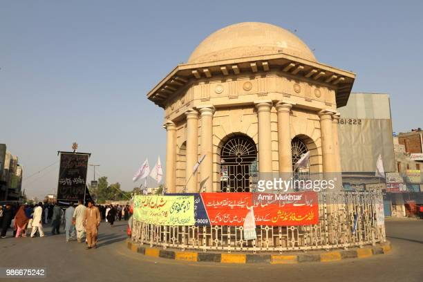 Pakistani Shia Muslims gathering and carrying flags near historical monument during a Muharram precession