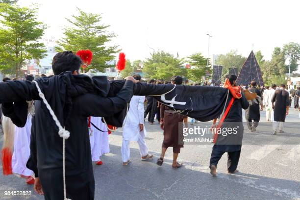 pakistani shia muslims march and carry the flags during a muharram precession on main road - depression sadness stock pictures, royalty-free photos & images