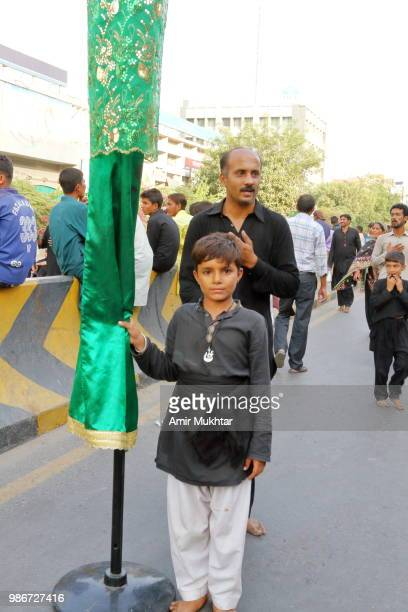 Pakistani Shia Muslims respecting and carry the sacred flags during a Muharram procession